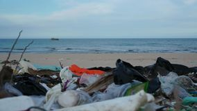 Garbage like plastic bottles and bags or other waste on polluted beach. Garbage like plastic bottles and bags or other waste lying on polluted beach stock video footage