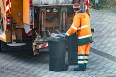 Garbage man collecting the bins