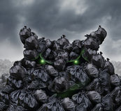 Garbage Monster. At a dump as mountains of black trash bags with an unpleasant smell shaped as an evil character with glowing green eyes and bad breath in an Stock Photo
