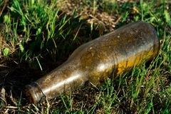 Garbage in nature, glass bottle lying on the floor. Environmental pollution stock photo