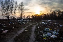 Garbage near the dirt road with sunset background Stock Image