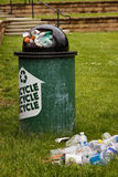 Garbage next to a recycle bin Stock Images