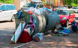 Garbage overfilled trash dumpsters in the street, surrounded by expensive cars Royalty Free Stock Image