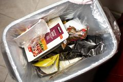 Garbage pail with trash. A trash can is partially filled with trash, featuring a an array of plastic articles royalty free stock photo