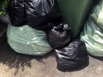 Garbage is pile lots dump, many garbage plastic bags black waste at walkway community village, pollution from trash plastic waste royalty free stock photos