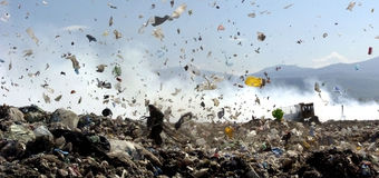 Garbage. Piles up in landfill site each day while truck covers it with sand for sanitary purpose Royalty Free Stock Image