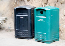 Garbage and Recycling Bins. A set of trash and recycling bins sitting together in a park Royalty Free Stock Photo