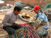 Garbage Recycling: Dealing With Wires. What happens with your garbage when you throw it out? Much of it is exported to developing countries. Here workers in stock photography