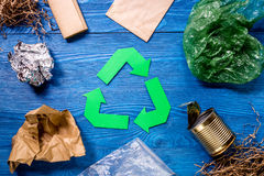Garbage for recycling with recycling symbol on blue wooden background top view.  Royalty Free Stock Photo