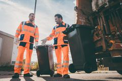 Garbage removal men working for a public utility. Emptying trash container stock photos