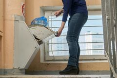 Garbage removal using a home garbage chute in Moscow dwelling house. Woman throwing away a garbage packed in a garbage bag using a home garbage chute in Moscow Stock Photos
