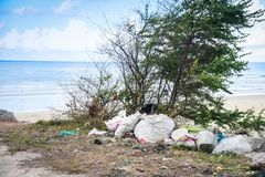 Environmental problem of plastic rubbish pollution in ocean. Garbage in the sea with bag plastic bottle and other garbage beach sandy dirty sea on the island / royalty free stock photography