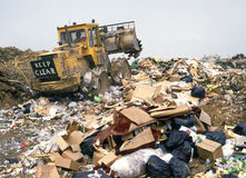 Garbage tip. Rubbish tip at landfill site with heavy duty compactor tractor shovel at work Royalty Free Stock Photography