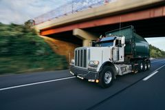 Garbage trash truck on highway motion blur concept. Commercial garbage truck hauling on highway concept with motion blur royalty free stock images