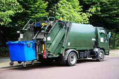 Garbage truck. Green garbage truck with an elevated blue wheelie bin at the rear stock photos