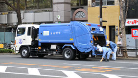 Garbage truck. Tokyo, Japan - 28 Dec, 2011: Garbage truck and salubrity workers on the streets of Tokyo Royalty Free Stock Photos
