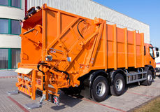Garbage truck. Back of an orange colored garbage truck Royalty Free Stock Photos