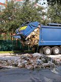 Garbage Truck Accident. Malfunction of garbage compacting mechanism leaves yucky garbage strewn on street and dripping out of back of truck royalty free stock photos