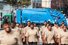 Garbage Truck Blocks Street As Anti Terrorism Precaution At Parade. Atlanta, GA, USA - November 11, 2017:  High School junior ROTC cadets march in the Georgia Royalty Free Stock Photo