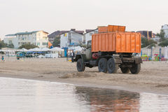 Garbage truck driving on the beach the sea coast in the early morning Royalty Free Stock Image