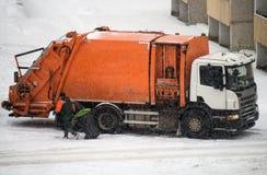 Garbage truck. Garbage truck takes away garbage in snowy weather Royalty Free Stock Image