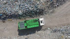 The garbage truck goes between the top of the garbage, aerial view. A green garbage truck goes between the mountains of garbage, top of the garbage stock video footage