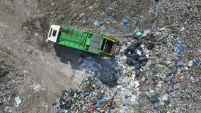 Extracting trash from garbage truck, aerial view. The garbage truck goes between the top of the garbage, aerial view, a green garbage truck goes between the stock footage