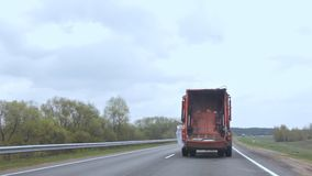 The garbage truck is moving along the road, the car that carries garbage is driving along the road. Container, garbage stock video