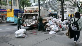 Garbage Truck in NYC and two DSNY workers Loading White Plastic Garbage Trash Bags into Truck. People on Sidewalk. Manhattan IV