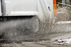 Garbage truck rides on big puddle in snowy day. Sleet splash on Royalty Free Stock Image