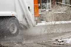 Garbage truck rides on big puddle in snowy day. Sleet splash on Royalty Free Stock Photo