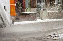 Garbage truck rides on big puddle in snowy day. Sleet splash on. A Manchester& x27;s road. England Stock Photography