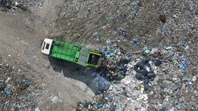 Garbage truck spills rubbish in a dump, aerial view. The garbage truck goes between the top of the garbage, aerial view, a green garbage truck goes between the stock video