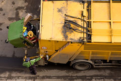 Garbage truck and worker. Yellow garbage truck with an elevated green wheelie bin at the rear Royalty Free Stock Photo
