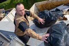 Garbage truck worker man collecting plastic industrial vehicle. Dustman Royalty Free Stock Images