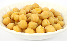 Garbanzo beans in bowl. A close view of garbanzo beans in an old white bowl royalty free stock photography