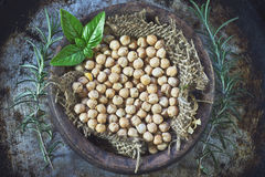 Garbanzo beans. (chickpeas) with basil in clay bowl on metallic rustic background. Top view royalty free stock photo