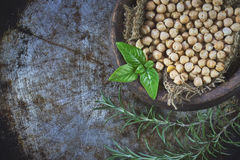 Garbanzo beans. (chickpeas) with basil in clay bowl on metallic rustic background. Top view with copy space royalty free stock photo