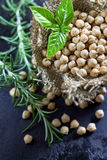 Garbanzo beans. (chickpeas) with basil in small burlap bag on black rustic background. Top view royalty free stock photos
