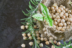 Garbanzo beans. (chickpeas) with basil in small burlap bag on black rustic background. Top view with copy space royalty free stock images