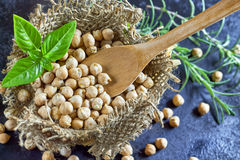 Garbanzo beans. (chickpeas) and wooden spoon with basil in small burlap bag on dark rustic background. Top view with copy space stock images