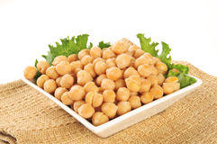 Garbanzo beans. A small bowl of garbanzo beans with a white background stock photography