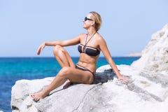 Garbnikująca blond kobieta w bikini i okularach przeciwsłonecznych przy morzem Zdjęcie Royalty Free
