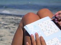 Garbnikująca dziewczyna bawić się sudoku na seashore Fotografia Royalty Free