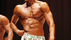 Garbnikujący bodybuilder pozuje na scenie przy sportową rywalizacją, perfect męski ciało zdjęcie wideo