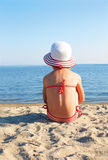 Garbnikujący dziewczyny obsiadanie na plaży w białym kapeluszu Zdjęcie Stock