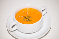 Garbuzova soup with sunflower seeds. Orange color in a white bowl Royalty Free Stock Images