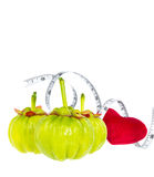 Garcinia cambogia fresh fruit with red heart and measuring tape,. Isolated on white. Garcinia is spice plants, contain high vitamin C and hydroxy citric acids Royalty Free Stock Photos
