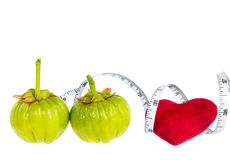 Garcinia cambogia fresh fruit with red heart and measuring tape,. Isolated on white. Garcinia is spice plants. It helps in the metabolism contain high vitamin C Stock Image