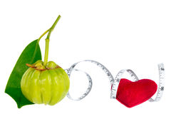 Garcinia cambogia fresh fruit with red heart and measuring tape,. Isolated on white. Garcinia is spice plants. It helps in the metabolism contain high vitamin C Royalty Free Stock Images